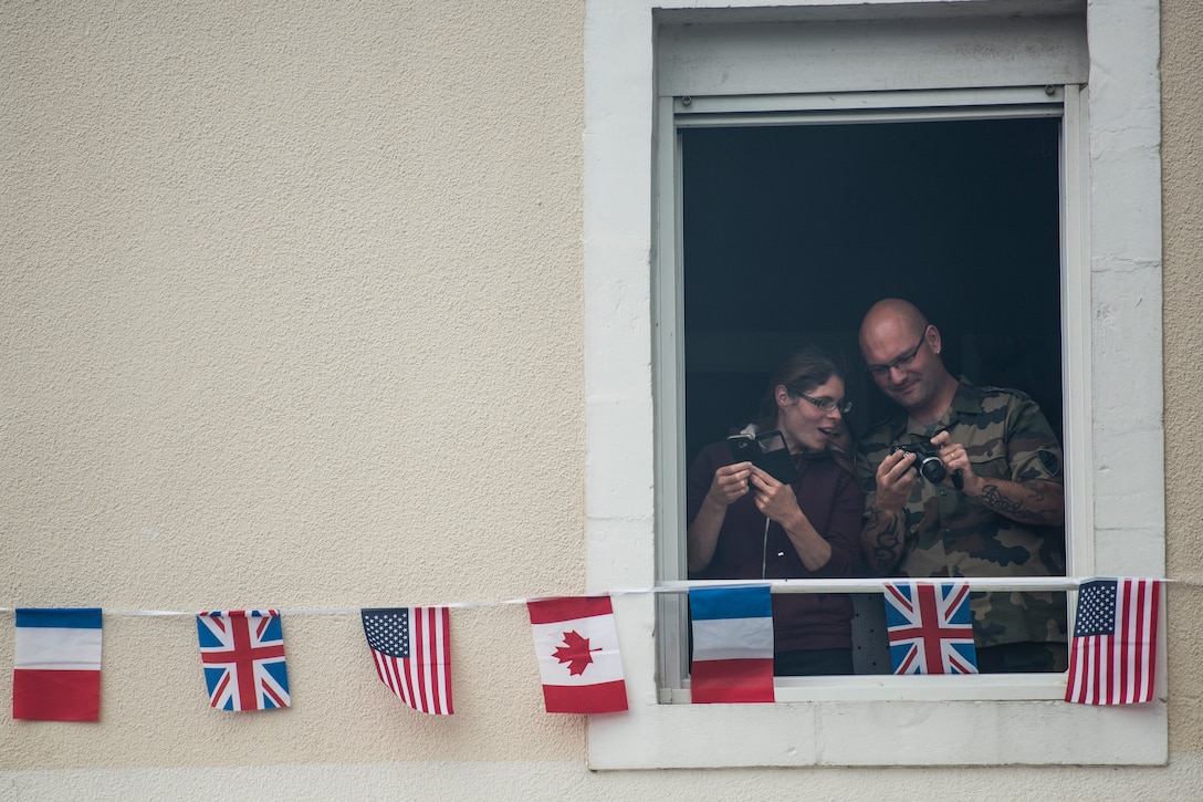 Two French locals, from their second story apartment, compare photos of the crowds gathered in the village square in Sainte-Mère-Église, France, June 6, 2019. To commemorate the 75th anniversary of D-Day, the village square was filled with events ranging from an 82nd Airborne ceremony to several C-130J Super Hercules flyovers. (U.S. Air Force photo by Senior Airman Kristof J. Rixmann)