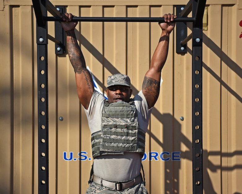 A first sergeant hangs from a pull-up bar