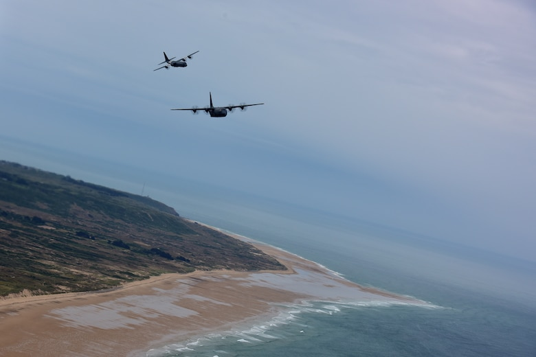 Aircraft fly in formation over the beaches of Normandy