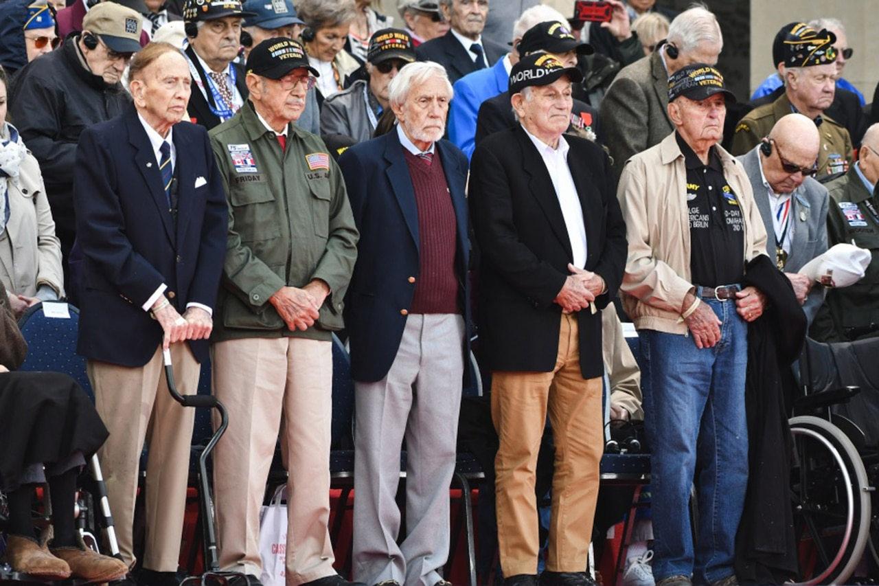 Five elderly male veterans stand in a row.