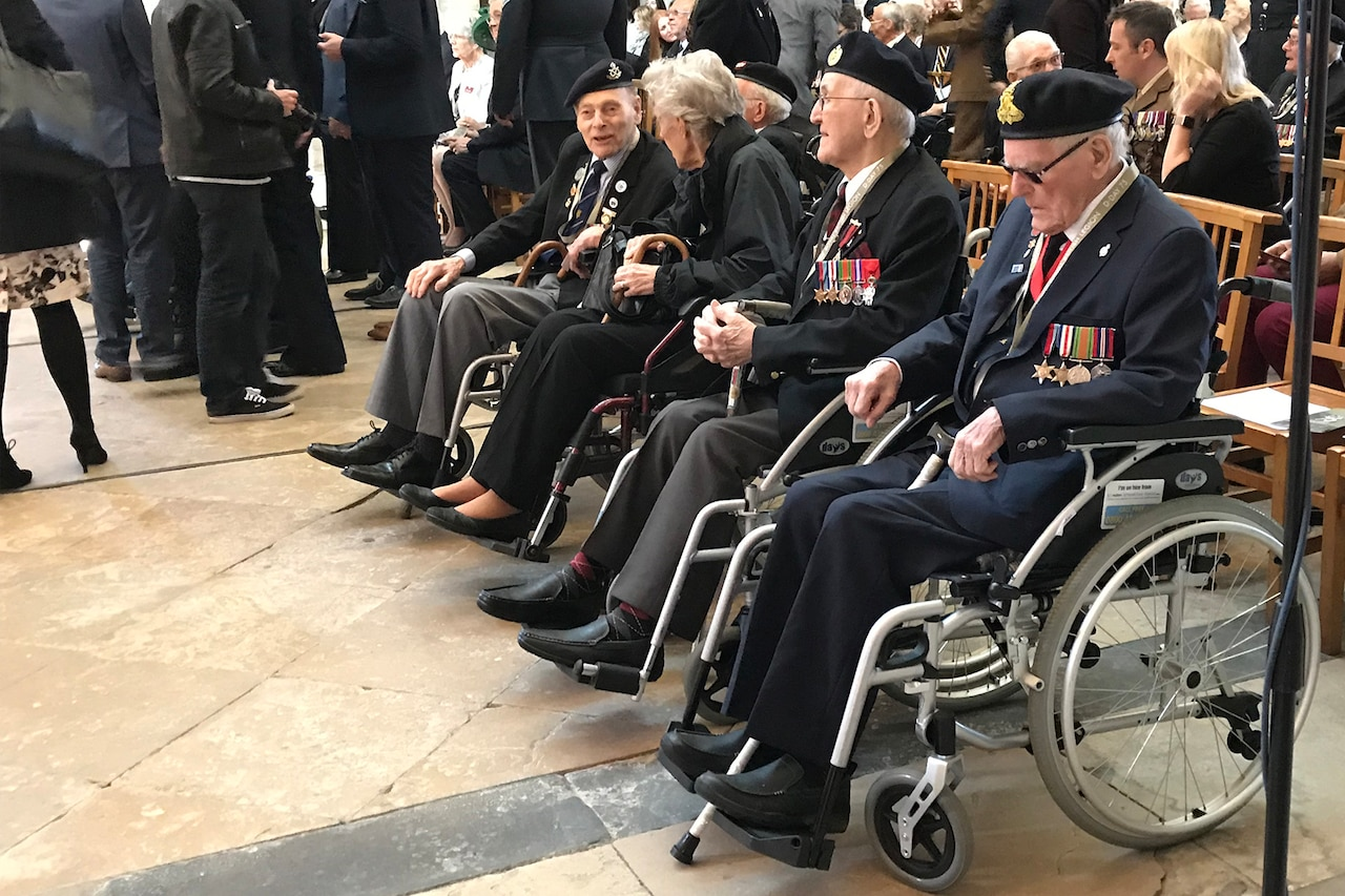 Four elderly men sitting in wheelchairs wear military medals.