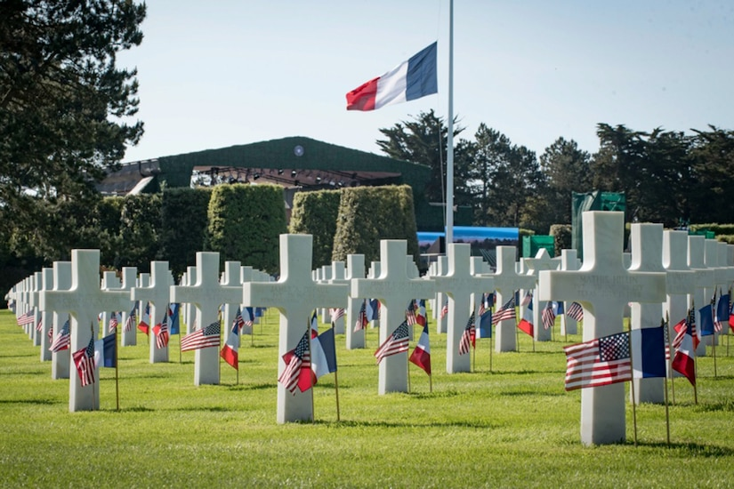 White crosses and small country flags mark graves in a cemetery.