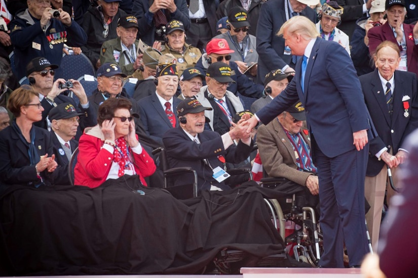 President Donald J. Trump shakes hands with a WWII veteran who is sitting in a wheelchair.