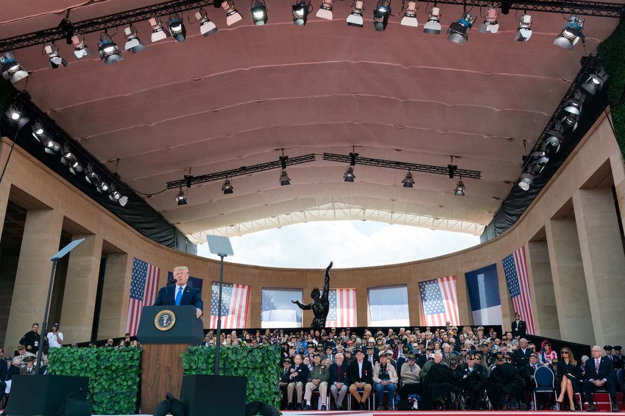 President Donald J. Trump speaks from a podium in a large hall surrounded by WWII veterans and American flags.