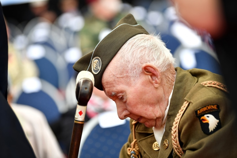 An elderly man wearing a military uniform hangs his head during a ceremony.