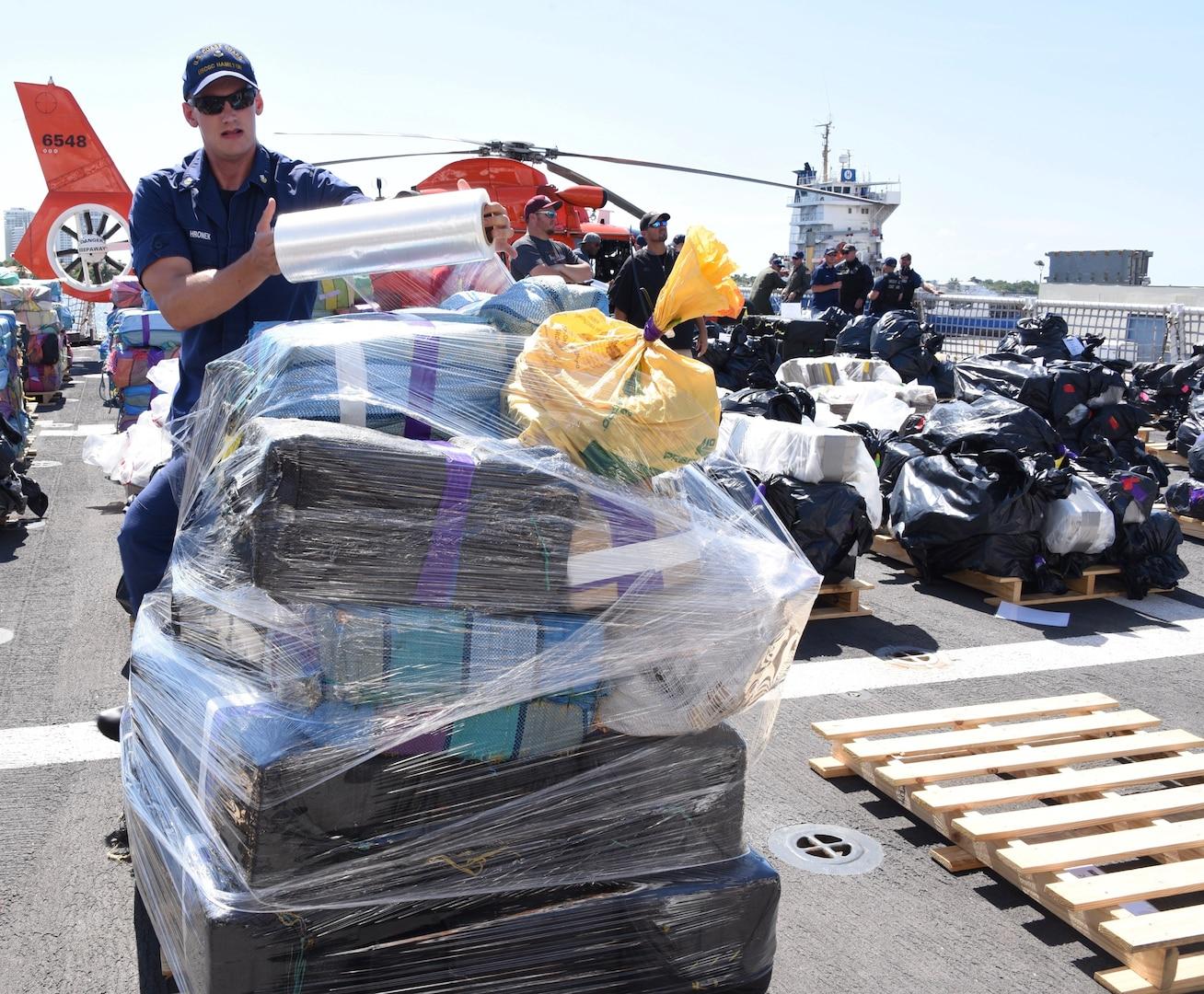 A Coast Guard Cutter Hamilton (WMSL-753) crewmember prepares a palette of interdicted cocaine.