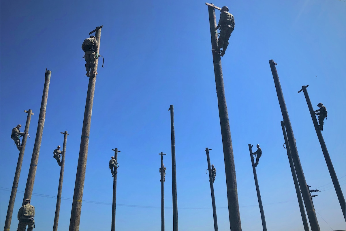 Navy Seabees practice working high above ground on utility poles.