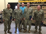 "Four of seven U.S. Navy ""Seabees"" who helped DLA save thousands through equipment transport: Petty Officer 2nd Class Vonell Williams, Petty Officer 2nd Class Matthew Klem, Chief Petty Officer William Wilson and Petty Officer 1st Class Justin Dickinson are pictured with Guam site chief Eric Mills."