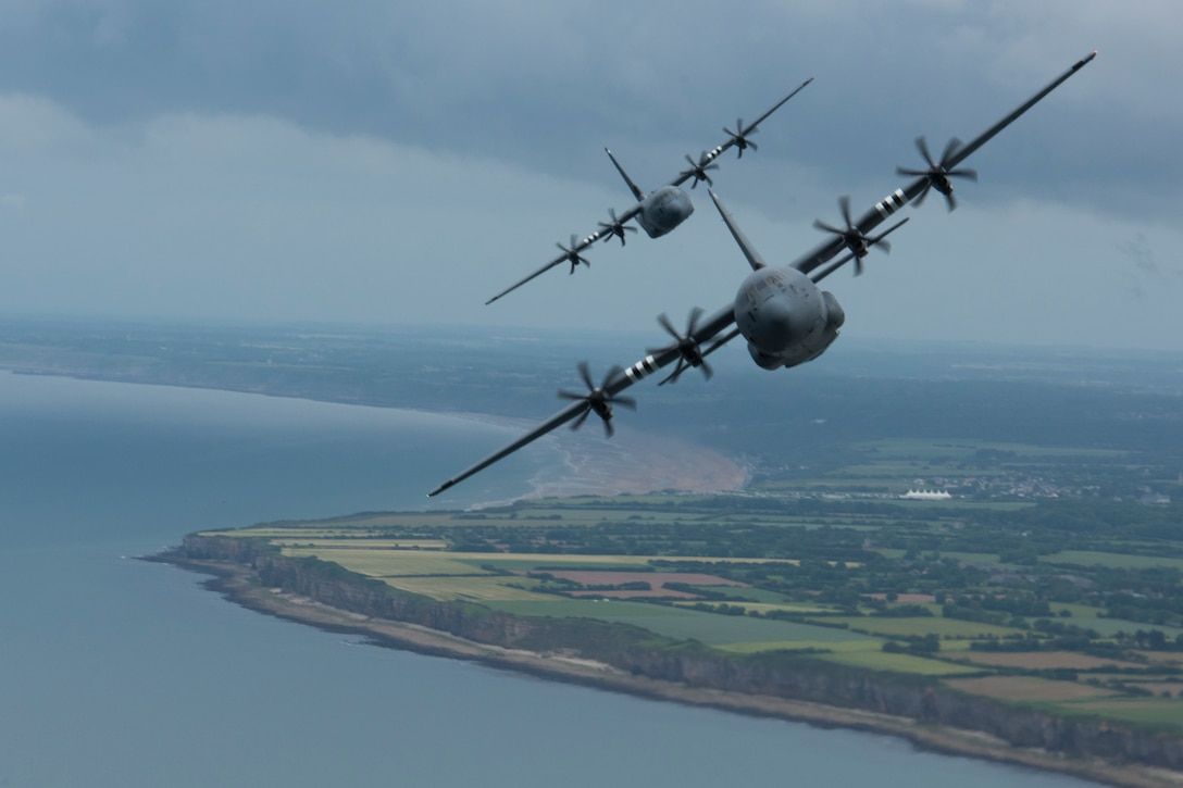 Two C-130J Super Hercules, belonging to the 37th Airlift Squadron on Ramstein Air Base, fly over Pointe-du-Hoc as part of a four-ship formation with a C-17 Globemaster III trailing a mile behind the formation in Normandy, France, June 5, 2019. Pointe-du-Hoc, coastal land featuring a 100 foot cliff overlooking the Atlantic Ocean, provided the highest vantage point between the American landing sectors at Utah and Omaha Beach on D-Day, June 6, 1944. The German army heavily fortified Pointe-du-Hoc as a result. Axis defenses notwithstanding, the U.S. Army Ranger Assault Group scaled the 100 foot cliff and soon after captured Pointe-du-Hoc. (U.S. Air Force photo by Senior Airman Kristof J. Rixmann)