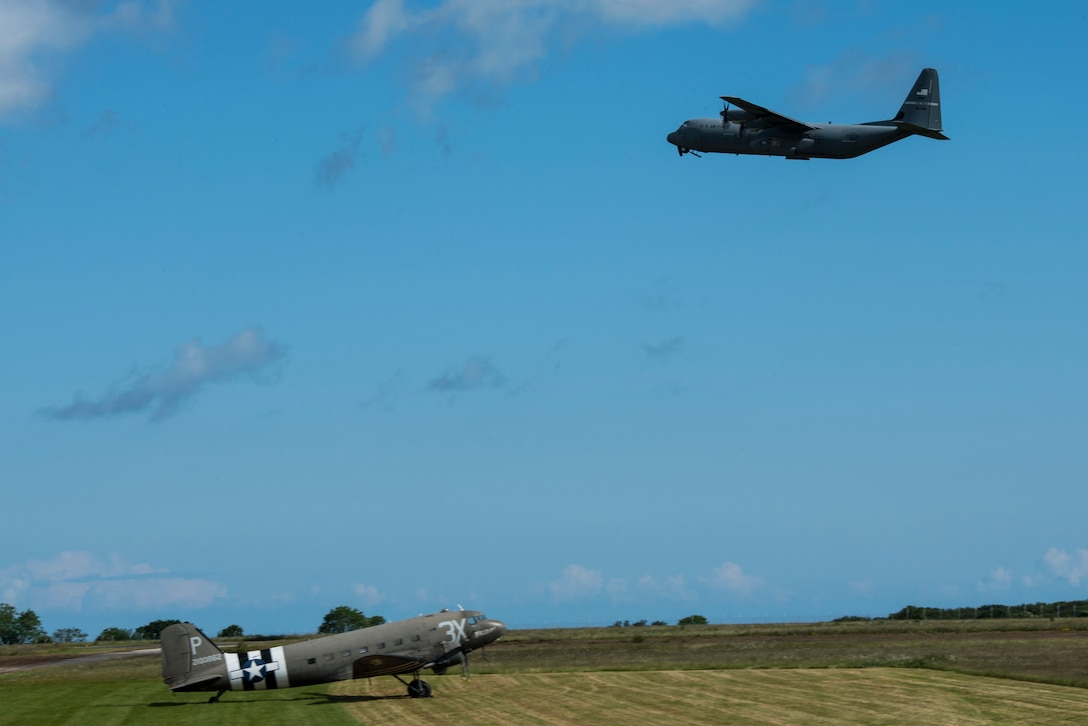 A U.S. Air Force C-130J Super Hercules, assigned to the 61st Airlift Squadron, Little Rock Air Force Base, Ark., flies over a Douglas C-47 Dakota at Cherbourg-Maupertus Airport, France, June 6, 2019. The 61st AS, draws lineage from the 61st Troop Carrier Squadron, which flew C-47s during the invasion of Normandy, 75 years ago. (U.S. Air Force photo by Senior Airman Devin M. Rumbaugh)