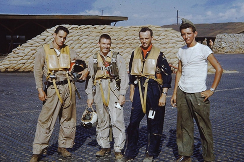 Four airmen pose for a picture on an air base.