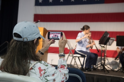Delores Goodwin, retired teacher and audience member, takes a video of the U.S. Air Force Heritage Winds June 6th, 2019, in Mount Pleasant, S.C.