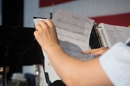 Airman 1st Class Louis Kim, a clarinet player with the U.S. Air Force Heritage Winds, changes his sheet music during a performance June 6th, 2019 in Mount Pleasant, S.C.