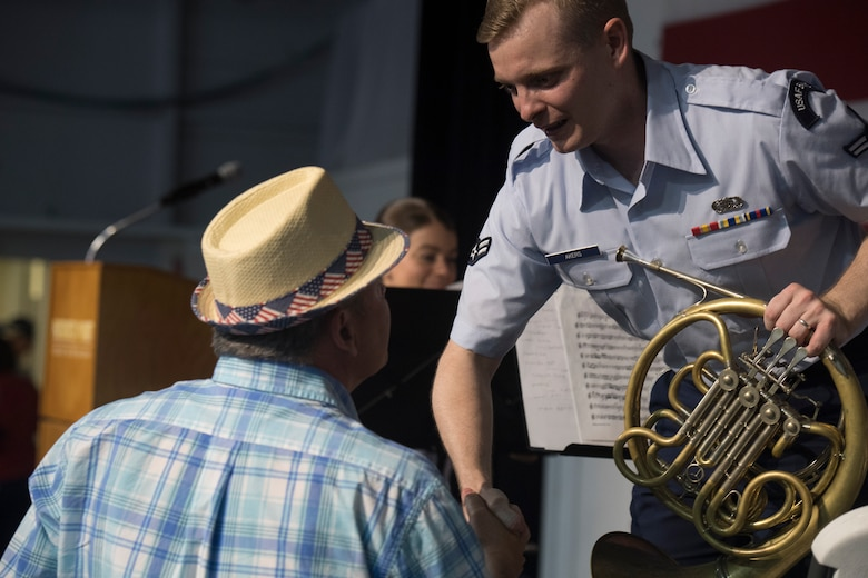 Airman 1st Class Derek Akers, a French horn player with the U.S. Air Force Heritage Winds, shakes hands with an audience member after a show June 6th, 2019, in Mount Pleasant, S.C.
