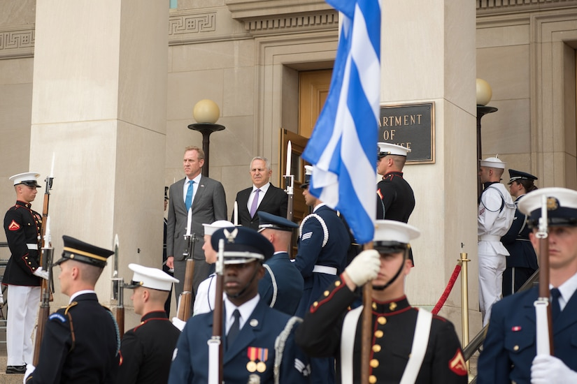 Acting Defense Secretary Patrick M. Shanahan and a Greek leader look out from a stairway at the entrance to a building as service members stand at attention.