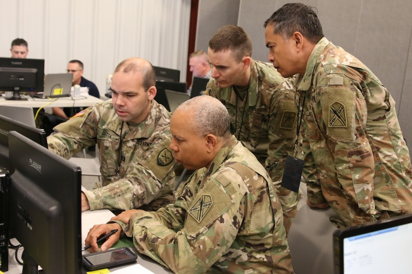 National Guard soldiers work at a computer.