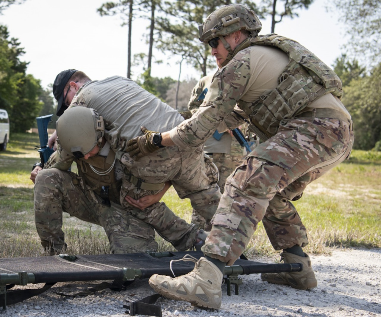 Service members help a simulated victim during an exercise.