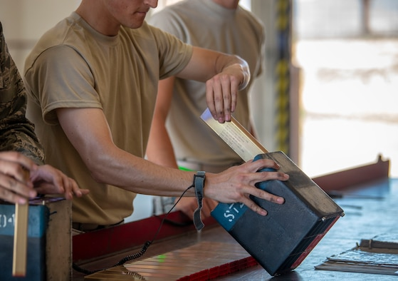 U.S. Air Force Airman 1st Class Mattias Jacobson, 57th Munitions Squadron line crew member, loads a mod so they can be delivered to the respected unit in need of the flares at Nellis Air Force Base, Nev., June 4, 2019. While handling flare mods, line delivery Airmen wear a band that grounds their hands to a copper wire to ensure no electric spark set off the flares. (U.S. Air Force photo by Staff Sgt. Tabatha McCarthy)