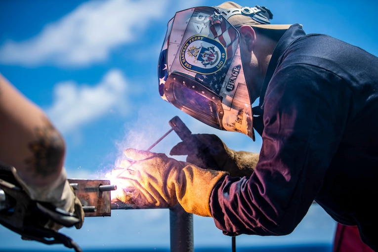A sailor wearing a mask uses a tool to weld.
