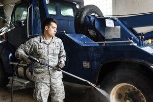 A man wearing the Airman Battle Uniform washes a truck.