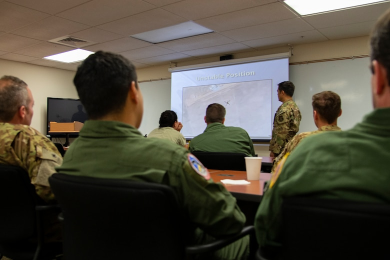 Tech. Sgt. Tony Fancher, a 302nd Airlift Wing Survival Evasion Resistance and Escape instructor, goes over emergency parachute procedures with members of the 731st Airlift Squadron and 34th Aeromedical Evacuation Squadron during a three-day Survival Evasion Resistance and Escape refresher training in Key West, Florida, May 23, 2019. (U.S. Air Force photo by Tech. Sgt. Frank Casciotta)