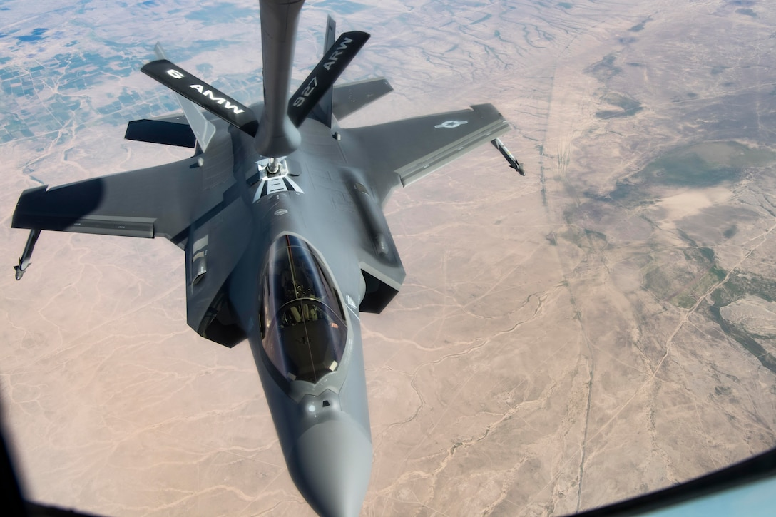 A fighter aircraft is refueled in mid-air over a desert-like landscape.