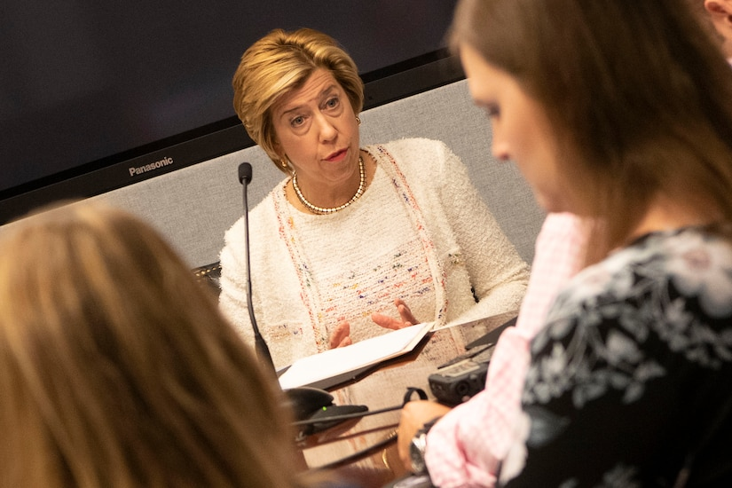 A woman speaks with members of the press.