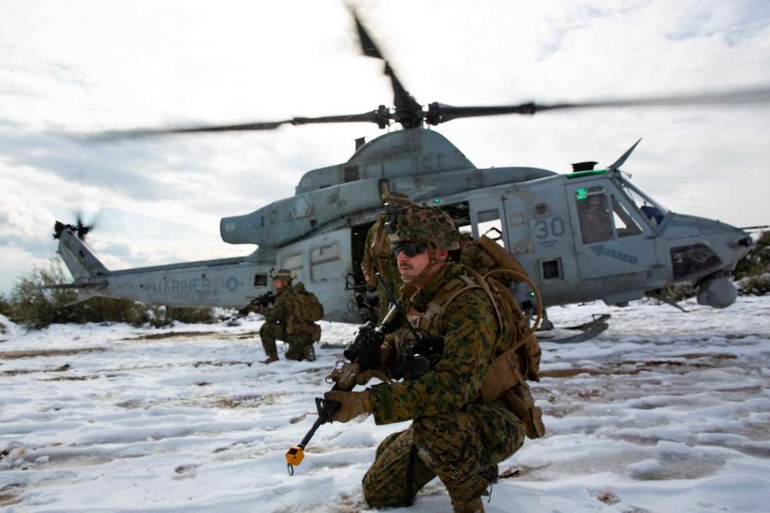 A service member with a rifle squats in the snow as other personnel exit a helicopter.