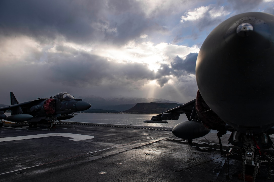 Two aircraft sit on the deck of a ship.