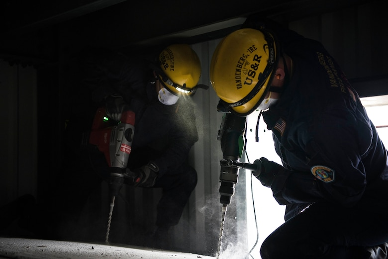Richard Strange and Luke McIntosh, 30th Civil Engineer Squadron firefighters, drill through concrete to rescue members in a trapped car during a base-wide earthquake exercise June 5, 2019, at Vandenberg Air Force Base, Calif. The exercise tested unit's readiness and ability to perform their duties in the face of natural disaster. (U.S. Air Force photo by Airman 1st Class Hanah Abercrombie)