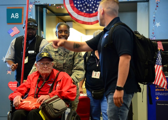 Airman First Class Cassandra Nyati, 377th Air Base Wing, escorts veteran Alfred Baye off his flight at the Sunport Airport, Albuquerque, N.M. June 7, 2019. Kirtland Airmen volunteered to assist with the three-day mission known as an Honor Flight, a mission conducted by non-profit organizations dedicated to transporting as many United States military veterans as possible to see the memorials of the respective war they fought in Washington, D.C. (U.S. Air Force photo by Jessie Perkins)