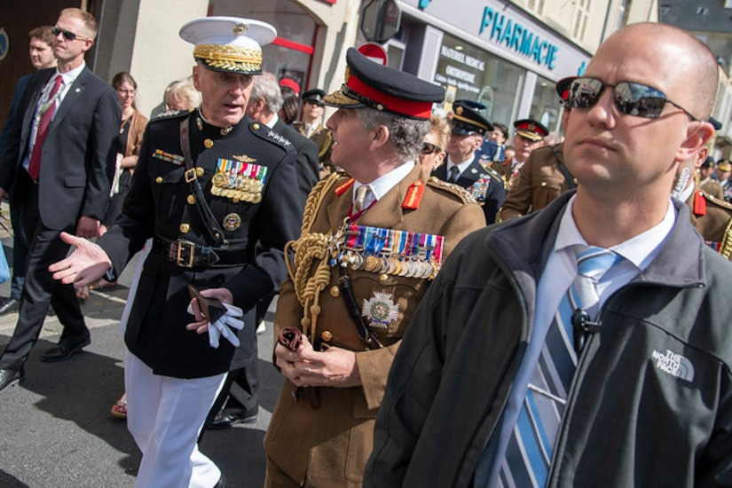 Senior military leaders speak to each other in French street.
