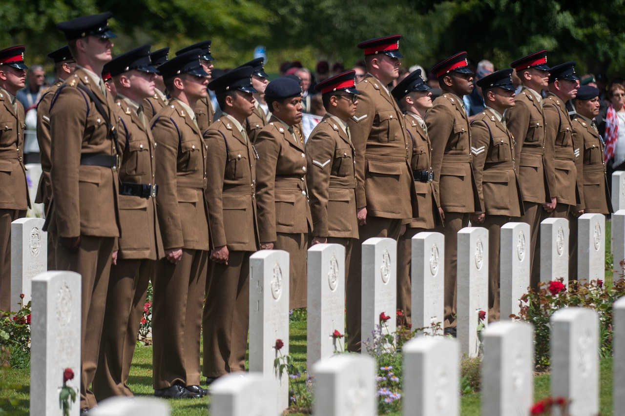 Soldiers in a line stand behind graves.