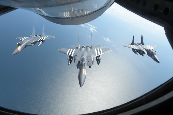 Three U.S. Air Force F-15s, assigned to the 48th Fighter Squadron at RAF Lakenheath, England, fly in formation behind a U.S. Air Force KC-135 Stratotanker off the Southern coast of England, June 6, 2019. The F-15s were painted with heritage markings in honor of the 75th anniversary of D-Day. As we commemorate D-Day 75, U.S. forces in Europe remain committed to collective defense and cooperative security alongside European allies and partners. (U.S. Air Force photo by Senior Airman Benjamin Cooper)
