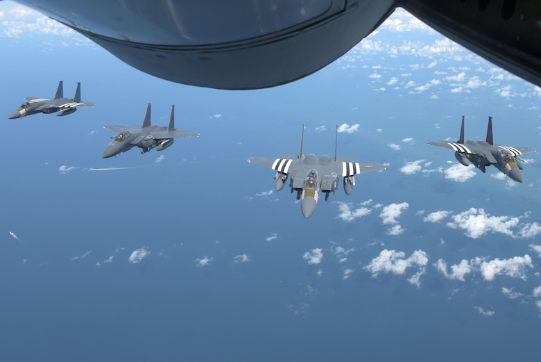 Four U.S. Air Force F-15s, assigned to the 48th Fighter Squadron at RAF Lakenheath, England, fly in formation behind a U.S. Air Force KC-135 Stratotanker off the Southern coast of England, June 6, 2019. The F15s were part of a commemorative 75th anniversary D-Day flyover in France. D-Day reflects the strength of enduring relationships and proven partnerships. This historic relationship has allowed U.S. forces to remain ready and have the strategic access in Europe to accomplish high-priority missions with our European allies and partners. (U.S. Air Force photo by Senior Airman Benjamin Cooper)