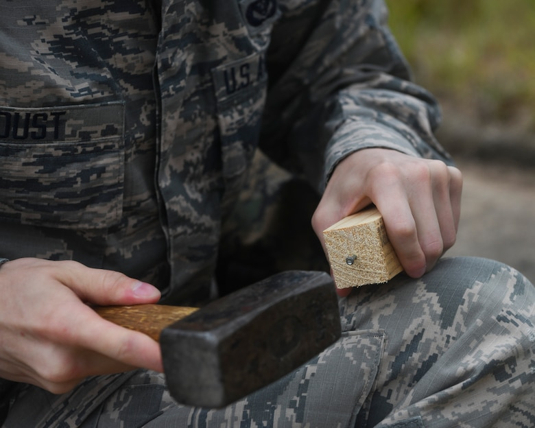Airman 1st Class Weston Foust, an engineering assistant from the 20th Civil Engineer Squadron at Shaw Air Force Base, S.C., hammers a nail into a stake while setting up global positioning receiver, June 5, 2019 at North Auxiliary Airfield, S.C. during an aircraft crash analysis exercise. Joint Base Charleston engineering assistants were joined by their counterparts from Shaw Air Force Base to help younger Airmen learn what it's like to coordinate with other bases during a real world crisis scenario. Air Force engineering assistants have the role of plotting out the positions of all debris pieces using global positioning devices during crash analysis operations. Engineering assistants specialize in planning and managing construction projects for bases and ensuring that facilities and structures are able to operate at full capacity.