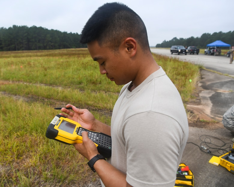 Airman 1st Class Jake Roxas, an engineering assistant assigned to the 628th Civil Engineer Squadron, S.C., calibrates a Trimble R8 global positioning receiver using a handheld unit, June 5, 2019 at North Auxiliary Airfield, S.C., during an aircraft crash assessment exercise. Airmen used specialized receivers that help them track the position of potential debris. Engineering assistants specialize in planning and managing construction projects for military installations and ensuring that facilities and structures are able to operate at full capacity.
