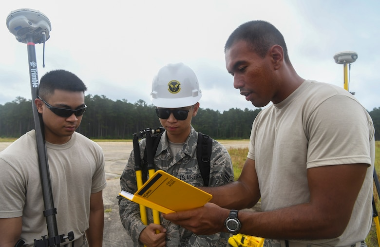 Airmen 1st Class Miguel Alano (right), Dave Ho (center) and Jake Roxas (left), engineering assistants with the 628th Civil Engineer Squadron, discuss the positions of simulated aircraft debris during a crash analysis exercise, June 5, 2019, at North Auxiliary Airfield, S.C. The exercise tested the readiness and critical thinking of Airmen that may have not experienced crisis situations before, while still maintaining a safe learning environment. Engineering assistants specialize in planning and managing construction projects for military bases and ensuring that facilities and structures are able to operate at full capacity.