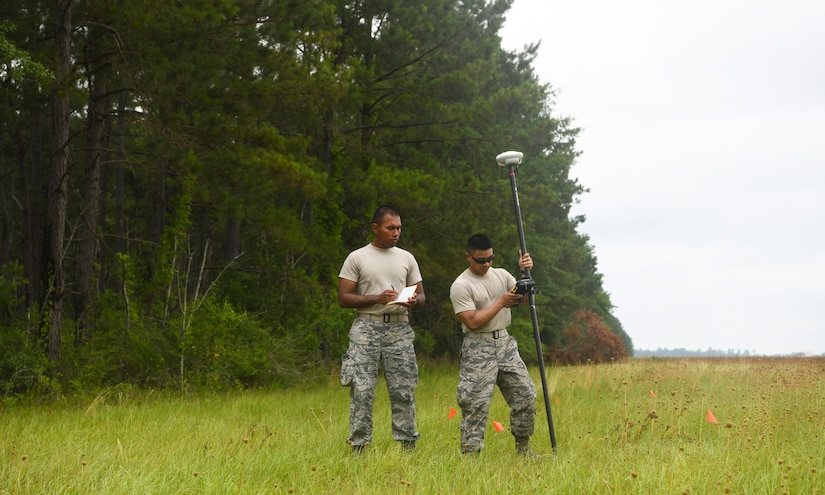 Airmen 1st Class Miguel Alano (left) and Jake Roxas (right), engineering assistants assigned to the 628th Civil Engineer Squadron, walk the field to determine the position of simulated aircraft wreckage, June 5, 2019 at North Auxiliary Airfield, S.C., during a crash assessment exercise. The exercise provided Airmen with the opportunity to practice on-seen protocols and to coordinate with other Airmen from Shaw Air Force Base, S.C., to completely map out debris in a simulated aircraft mishap. Air Force engineering assistants have the role of plotting out the positions of all debris pieces using global positioning devices during crash analysis operations. Engineering assistants specialize in planning and managing construction projects for bases and ensuring that facilities and structures are able to operate at full capacity.