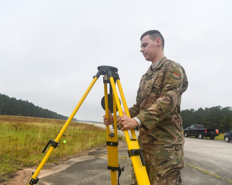 U.S. Air Force Staff Sgt. Kennith Hopkins, an engineering assistant from the 20th Civil Engineer Squadron at Shaw Air Force Base, S.C., sets up a tripod during an aircraft crash analysis exercise June 5, 2019, at North Auxiliary Airfield, S.C. Joint Base Charleston engineering assistants were joined by their counterparts from Shaw Air Force Base to help younger Airmen learn what it's like to coordinate with other bases during a real world crisis scenario. Air Force engineering assistants have the role of plotting out the positions of all debris pieces using global positioning devices during crash analysis operations. Engineering assistants specialize in planning and managing construction projects for military installations and ensuring that facilities and structures are able to operate at full capacity. (U.S. Air Force photo by Senior Airman Cody R. Miller)