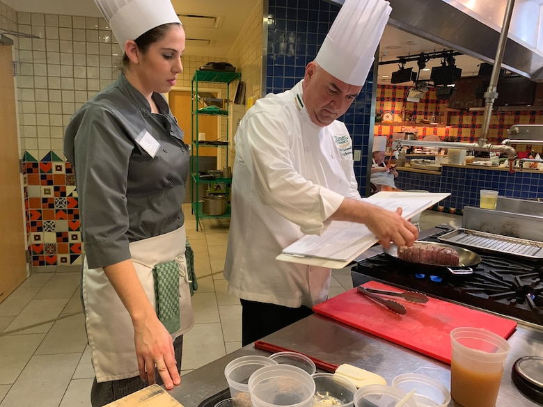 Culinary Institute of America San Antonio Chef Will Packwood and Gabriela Irwin, a chef at Spangdahlem Air Base, Germany, look over a pork loin recipe during the practical portion of the first Air Force Techniques of Healthy Cooking Course June 5, 2019, in San Antonio. Sixteen nonappropriated fund food and beverage chefs and cooks from across the Air Force attended the course established by the Air Force Services Center, in partnership with the CIA San Antonio. The five-day course is designed to teach and demonstrate healthier ingredients, flavorful spicing and better cooking methods to deliver healthier menu choices at food service operations across installations, not just at dining facilities. (U.S. Air Force photo by Debbie Aragon)