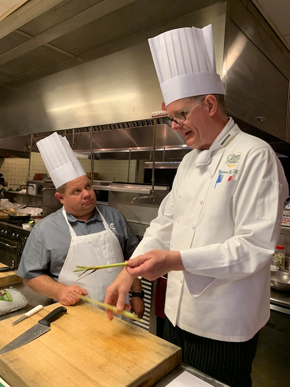 Culinary Institute of America Chef Hinnerk von Bargen demonstrates how to prepare lemon grass for chopping to cook Justin Lentz from Buckley Air Force Base, Colorado, during the practical portion of the new Air Force Techniques of Healthy Cooking Course at the CIA San Antonio campus, June 5, 2019. Lentz and 15 other nonappropriated fund employees from across the Air Force attended the course established by the Air Force Services Center, in partnership with the CIA San Antonio. The five-day course is designed to teach and demonstrate healthier ingredients, flavorful spicing and better cooking methods to deliver healthier menu choices at food service operations across installations, not just at dining facilities. (U.S. Air Force photo by Debbie Aragon)