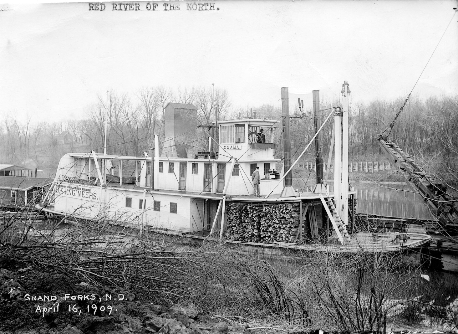 steamer with wood on deck in narrow river