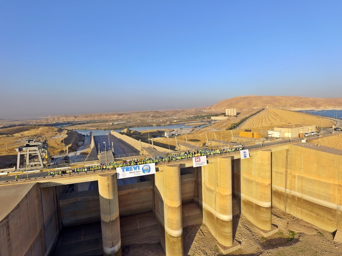 The men and women of the Mosul Dam Task Force stand on the top of the Mosul Dam spillway.  The Mosul Dam Project was a 3-year partnership started in 2016 as a joint venture among the Iraq Ministry of Water Resources, the U.S. Army Corps of Engineers, and Italian Company Trevi S.p.A. in an effort to stabilize and repair the dam, and update the infrastructure of the dam.The dam sits in a valley along the Tigris River approximately 30 miles outside Mosul City in Iraq. It is the largest dam in Iraq, and the fourth largest in the Middle East, and supplies water, hydropower, irrigation and flood control to the region.