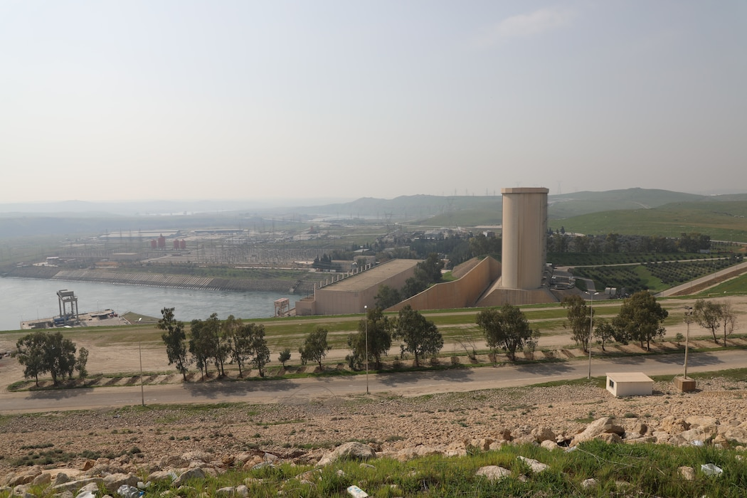 Mosul Dam, with its the hydropower plant and four water storage towers, sits in a valley along the Tigris River 30 miles outside Mosul City in Iraq.. It is the largest dam in Iraq, and the fourth largest in the Middle East and supplies water, hydropower, irrigation and flood control to the region.