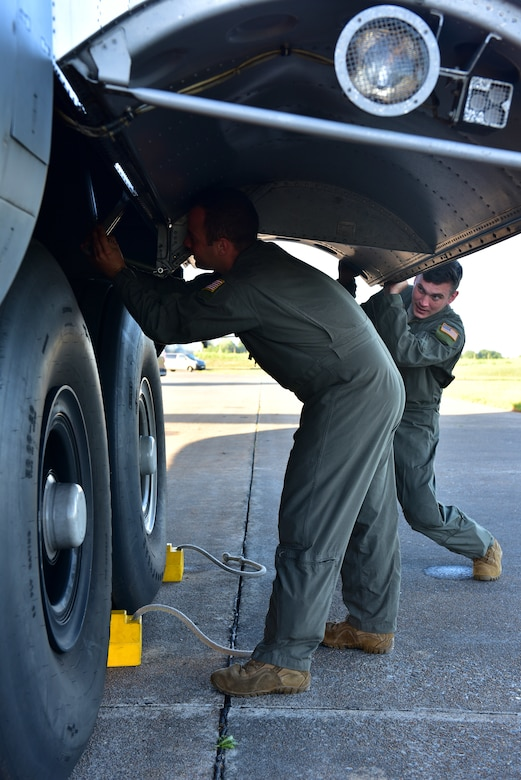 Two Airmen inspect the tire of a C-130J
