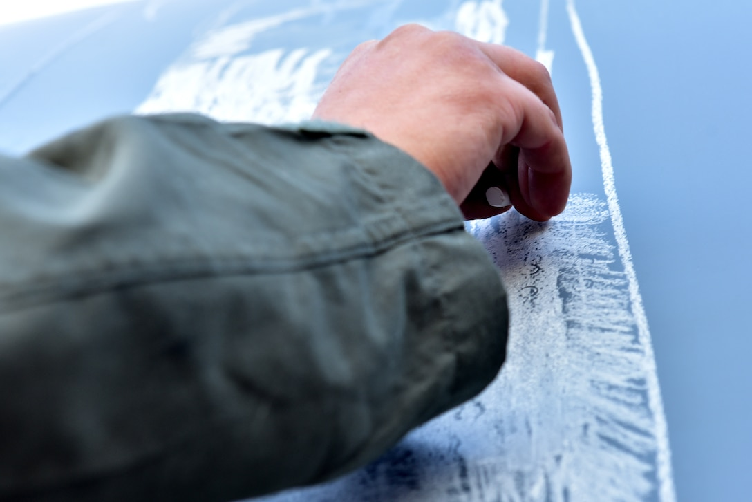 An Airman draws with chalk on the side of a C-130J