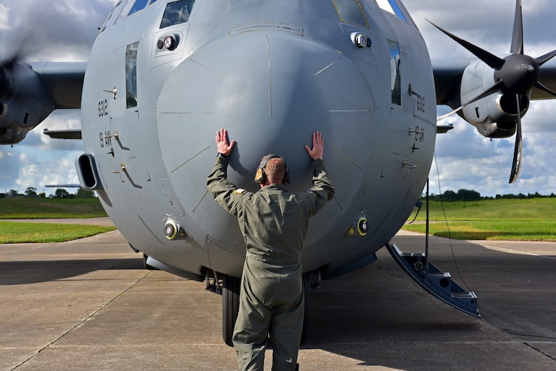 An Airman hugs the nose of a C-130J