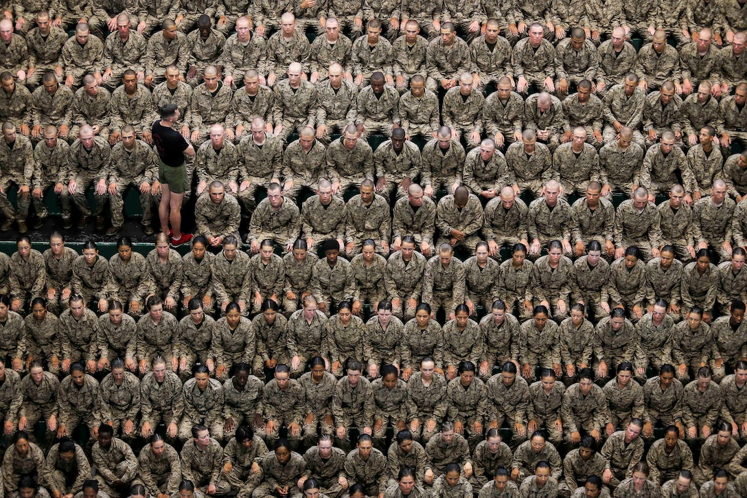 A swim instructor wearing a black shirt stands among dozens of seated Marine recruits in uniform.
