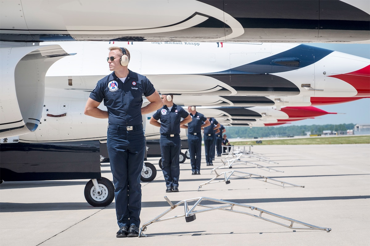 Members of the Thunderbirds, the Air Force's flight demonstration team, stand in a row next to aircraft.